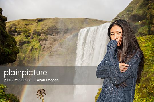 beautiful woman posing at Skogarfoss waterfall in Iceland - p1166m2200208 by Cavan Images