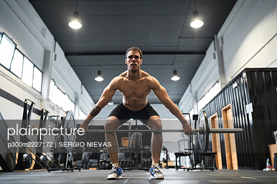 Male athlete picking up barbell in gym - p300m2227172 by SERGIO NIEVAS