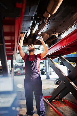 Male mechanic working under car in auto repair shop - p1023m2196754 by Tom Merton