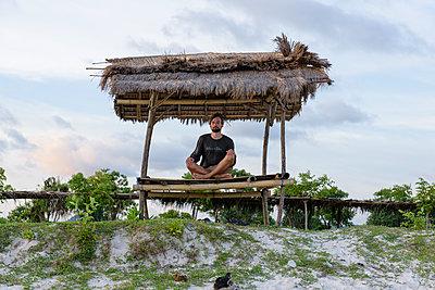 Mann meditiert am Strand - p1273m1556528 von melanka