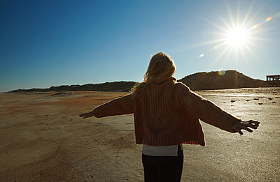 Blonde woman turns towards the sun with an outstretched arms - p1577m2150344 by zhenikeyev