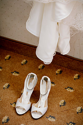 High angle view of sandals on tiled floor under wedding dress at home - p300m2143555 by Daniel Waschnig Photography