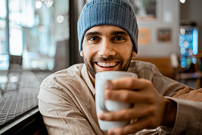 Happy mid adult man holding coffee cup in cafe - p300m2277387 by Rafa Cortés