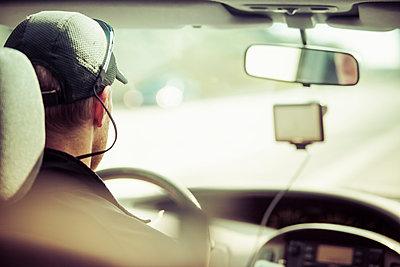 Rear view of man driving car - p426m1062494f by Katja Kircher