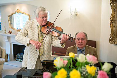Two senior men playing music together - p1026m1164195 by Patrick Frost