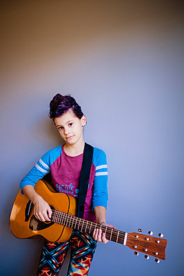 Portrait of girl playing guitar while standing by wall at home - p1166m1577803 by Cavan Images