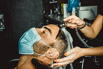 beautician and hairdresser working with mask for the covid19 virus - p1166m2200261 by Cavan Images