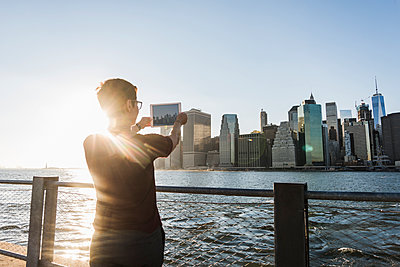 USA, Brooklyn, back view of woman taking picture of Manhattan skyline with tablet - p300m1205111 by Uwe Umstätter