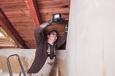 Roof insulation, worker drilling wooden board with a cordless drill - p300m2084079 by Sebastian Dorn