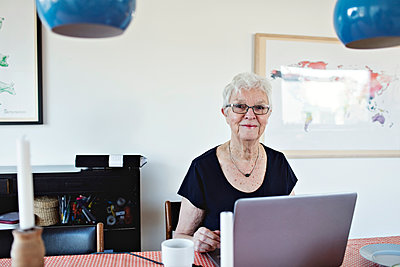 Portrait of smiling retired senior woman sitting with laptop at dining table - p426m1569811 by Maskot