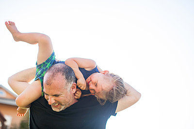 Father and son fooling around, outdoors, father carrying son over shoulders - p924m1422665 by Sasha Gulish