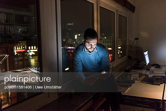 Businessman sitting on window sill in office at night using tablet - p300m1581406 von Uwe Umstätter