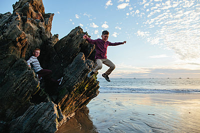 Playful boy jumping at beach while brother sitting on rocks - p1166m1546856 by Cavan Images