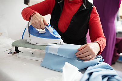 woman ironing a blue cloth - p1166m2131024 by Cavan Images