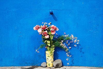 Plastic flowers in front of blue wall - p161m902883 by Kerstin Schomburg