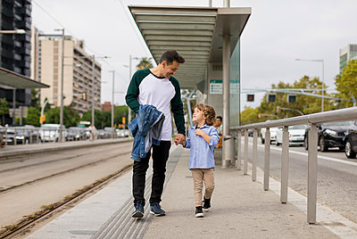 Smiling father and son walking hand in hand at tram stop in the city - p300m2070403 von Mauro Grigollo