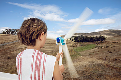 Girl looking at small wind turbine on white wall - p300m2156513 by Maya Claussen