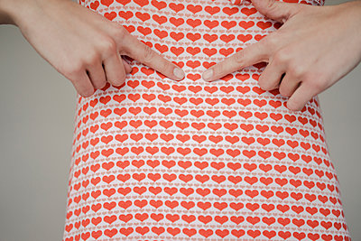 Woman pointing at heart-shaped pattern of her dress - p586m1548260 by Kniel Synnatzschke