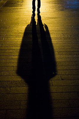 Mysterious shadowy figure in the city at night  - p794m2064417 von Mohamad Itani