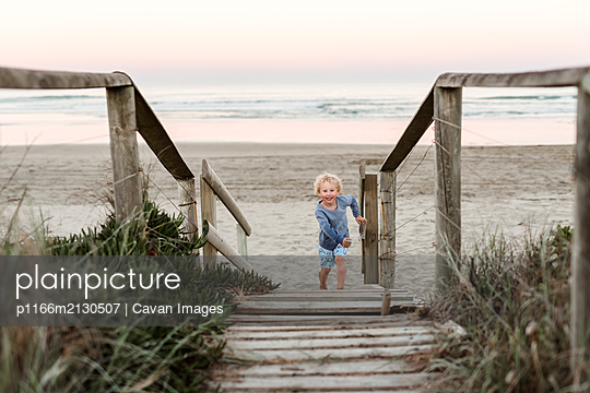 Little boy with curly hair on wooden path at beach - p1166m2130507 by Cavan Images