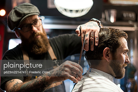 Hairdresser cutting man's hair in salon - p623m2214741 by Frederic Cirou