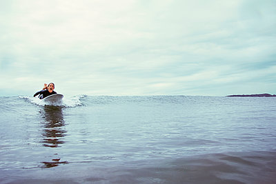 Excited young woman surfing on sea against cloudy sky - p1166m1150448 by Cavan Images