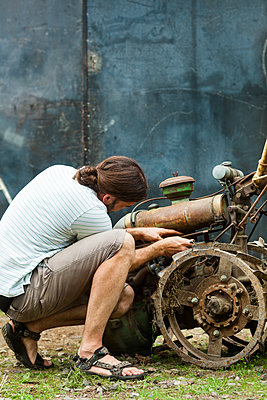 Man working on old rusty machine outdoors - p312m1552659 by Johner