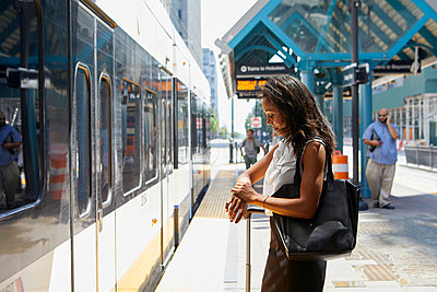 Businesswoman checking time by light rail line - p924m2018641 by Megan Maloy