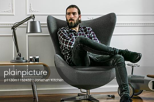 Mann sitzt in einem Sessel - p1130m1152432 von Jonathan Kitchen