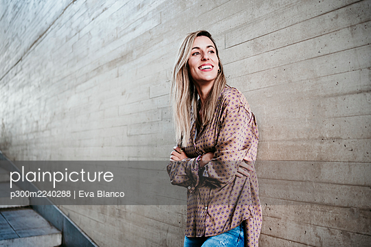 Happy beautiful woman with arms crossed looking away while leaning on wall - p300m2240288 by Eva Blanco