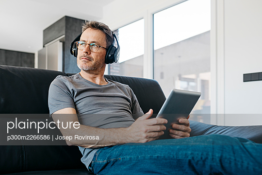 Mature man with digital tablet looking away while listening music through headphones on sofa in living room - p300m2266586 by Josep Rovirosa