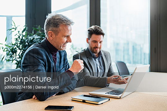 Smiling male entrepreneurs discussing over laptop while working in office - p300m2274156 by Daniel Ingold