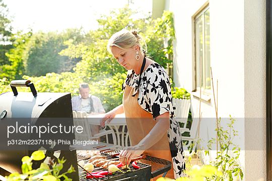 Woman preparing food on barbecue in garden - p312m2237118 by Phia Bergdahl