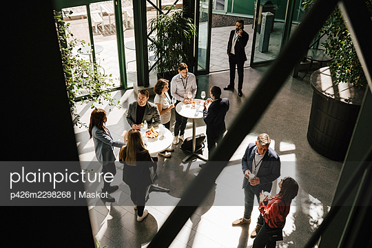 High angle view of multi-ethnic business professionals discussing together during seminar at convention center - p426m2298268 by Maskot