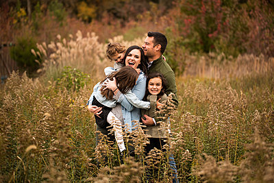 Parents enjoying with daughters while standing amidst plants against trees in forest - p1166m2034618 by Cavan Images