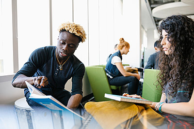 Students discussing text book in univeristy library - p1192m2110062 by Hero Images