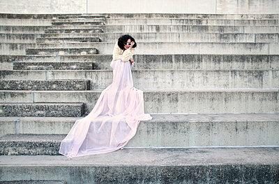 Frau mit rosa Rock auf einer Treppe sitzend - p1452m1513127 von Alessia Rollo
