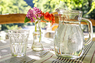 Glass jar and glass of water on table - p300m1581691 von Maria Maar