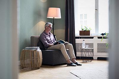Mature man reading magazine at home - p300m2070706 by Rainer Berg