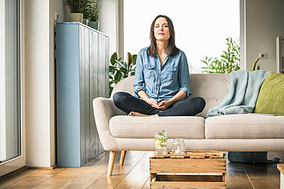 Woman sitting on the couch at home with closed eyes - p300m2104412 by Uwe Umstätter