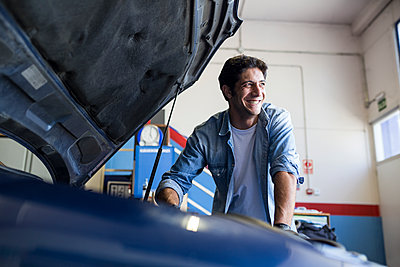 Smiling man working with engine of car in repair service and looking away - p300m2155110 by Andrés Benitez