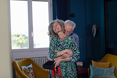 Senior man embracing smiling woman while standing at home - p300m2266058 by Emma Innocenti