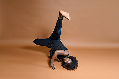 African woman with Afro hairdo practices gymnastics - p427m2285219 by Ralf Mohr