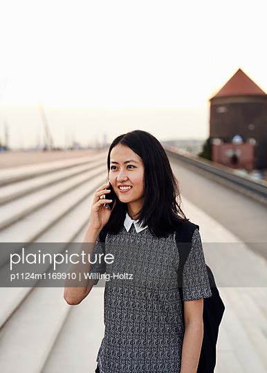 Asiatin telefoniert auf dem Arbeitsweg - p1124m1169910 von Willing-Holtz