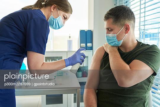 Side view of a man during the vaccination procedure, Poland, podkarpackie, Dębica - p300m2287099 von gpointstudio