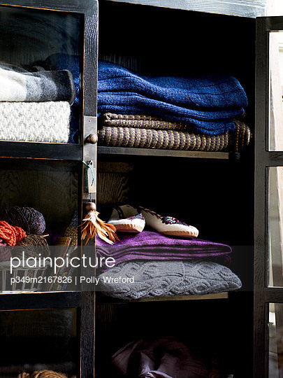 Cabinet with woollen blankets and wool - p349m2167826 by Polly Wreford