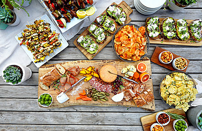 High angle view of various food served on wooden table - p1166m2000846 by Cavan Images