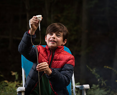 Boy taking a roasted marshmallow off of a metal stick outdoors. - p1166m2214646 by Cavan Images
