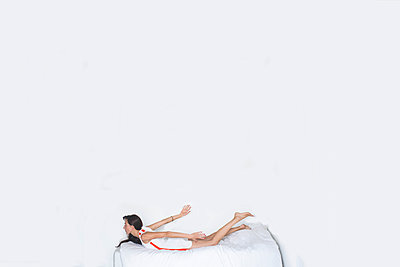Woman lying on bed - p1413m2008471 by Pupa Neumann