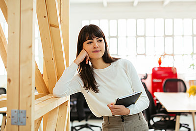 Smiling young woman with tebook in office - p300m1587385 by Bonninstudio